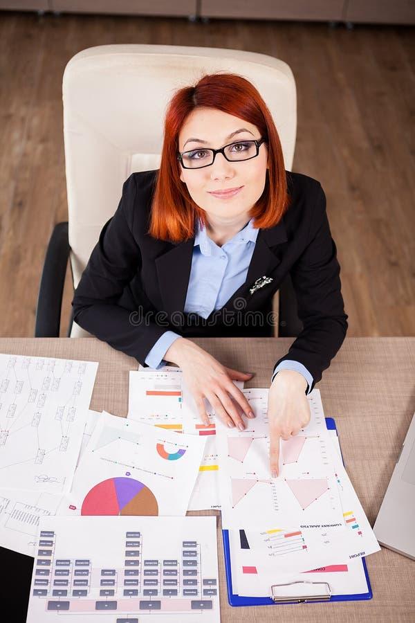 Femme d'affaires recherchant avec des diagrammes sur la table photo stock