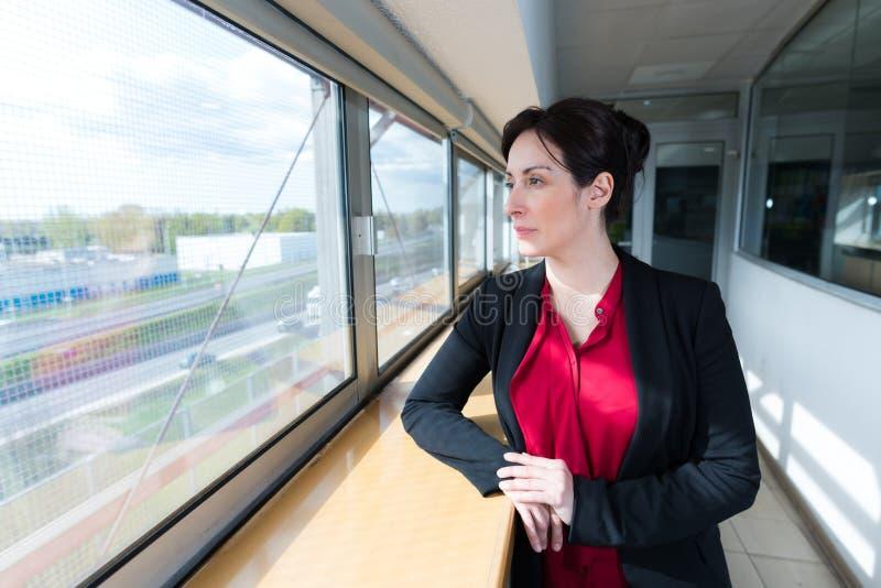 Femme d'affaires regardant dehors par la fenêtre fermée photographie stock libre de droits