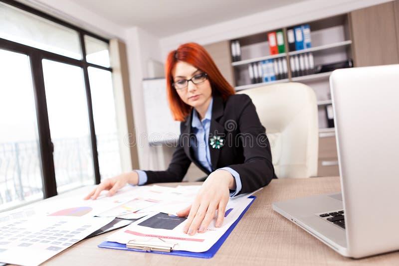 Femme d'affaires regardant des diagrammes et des diagrammes dans son bureau photographie stock