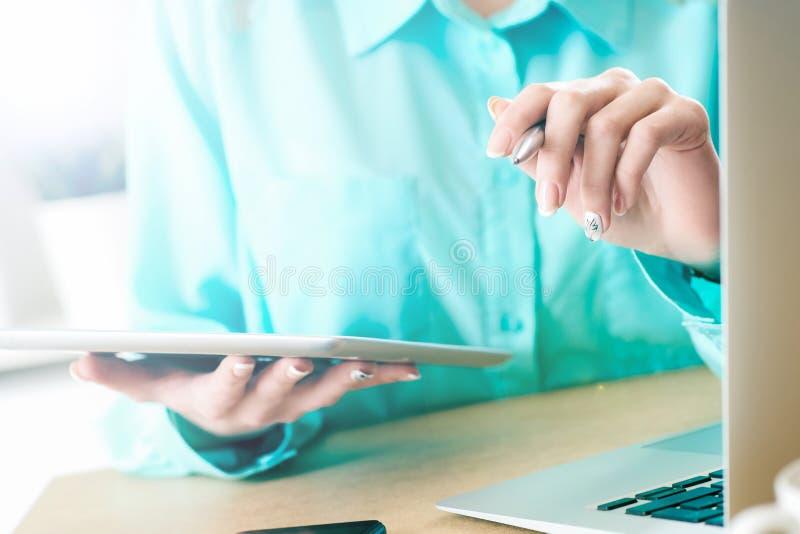 Femme d'affaires regardant et étudiant des statistiques sur le plan rapproché d'affichage de comprimé La main gauche femelle tien photos libres de droits