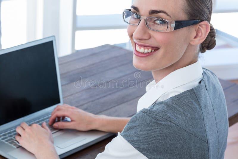 Download Femme D'affaires Regardant L'appareil-photo Avec Des Verres Et à L'aide De L'ordinateur Portable Image stock - Image du chic, ordinateur: 56480885