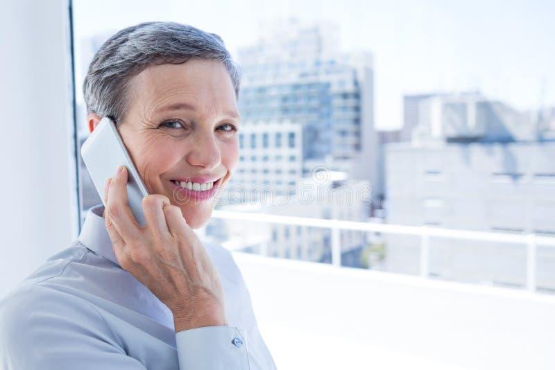 Download Femme D'affaires Regardant L'appareil-photo Tandis Qu'au Téléphone Photo stock - Image du élégant, heureux: 56483412