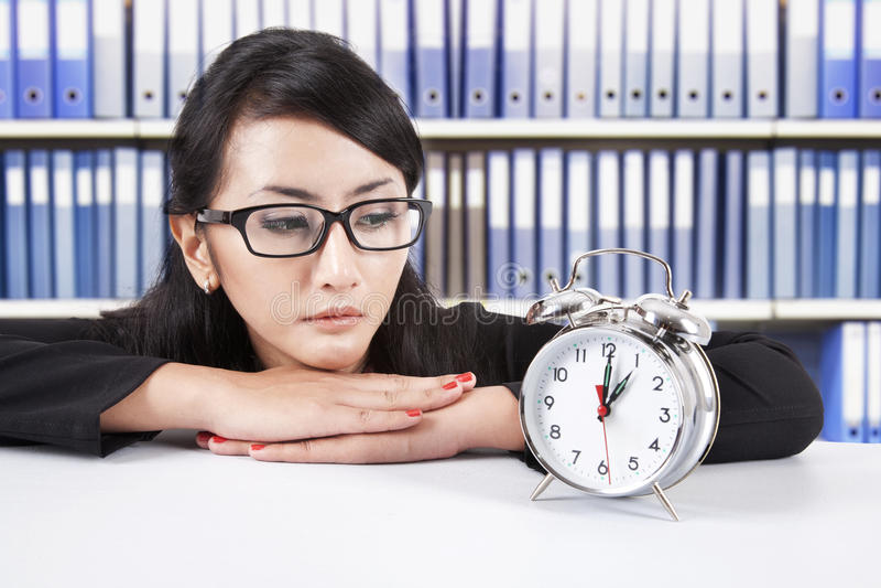 Femme d'affaires regardant l'horloge d'alarme photo stock