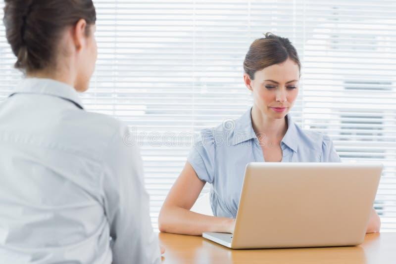 Femme d'affaires regardant l'ordinateur portable pendant une entrevue photo stock