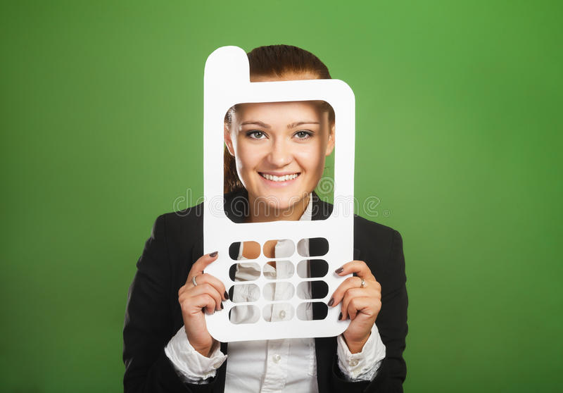 Femme d'affaires regardant par le téléphone portable de papier sur le backg vert images stock