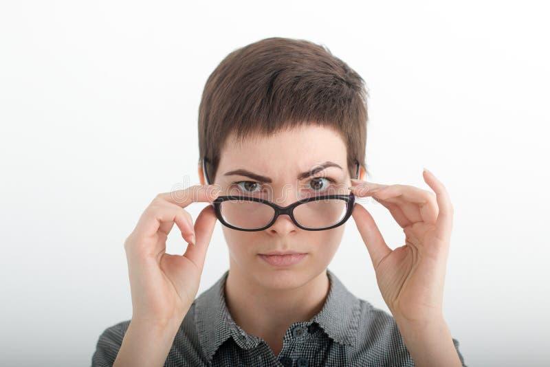 Femme d'affaires regardant sévèrement au-dessus de ses verres Portrait de femme à la mode de brune, regardant l'appareil-photo images libres de droits