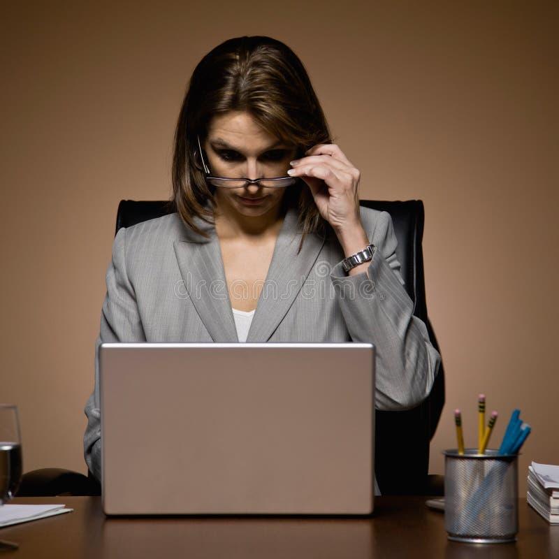 Femme d'affaires retirant des lunettes, fonctionnant tard photographie stock
