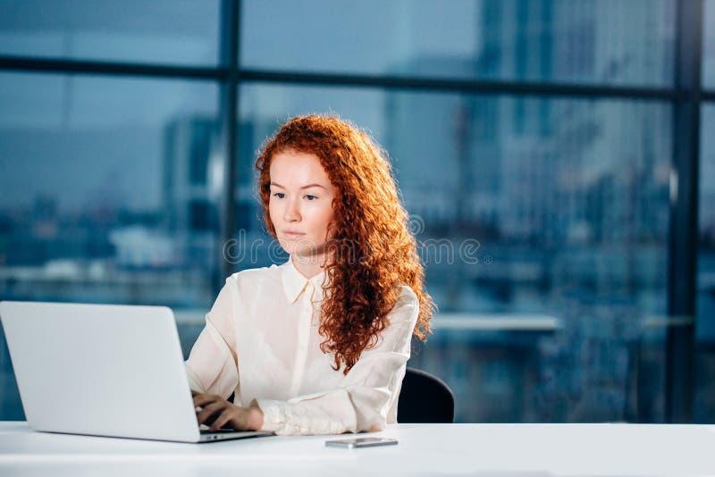 Femme d'affaires rousse s'asseyant au poste de travail moderne lumineux et dactylographiant sur l'ordinateur portable photos libres de droits