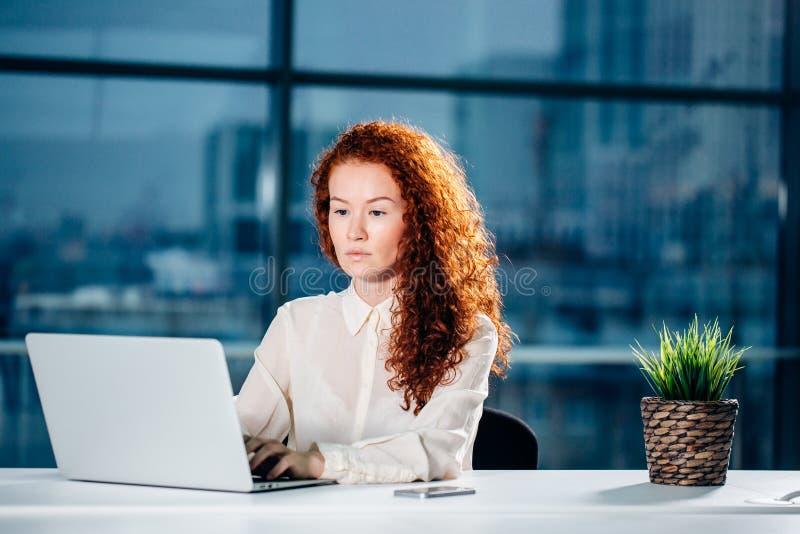 Femme d'affaires rousse s'asseyant au poste de travail moderne lumineux et dactylographiant sur l'ordinateur portable images stock