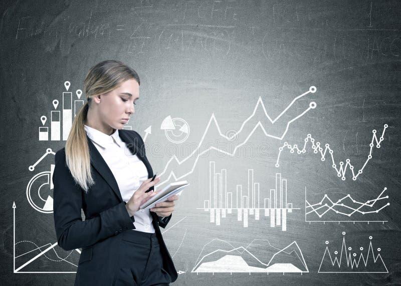 Femme d'affaires sérieuse avec un planificateur, graphiques photographie stock