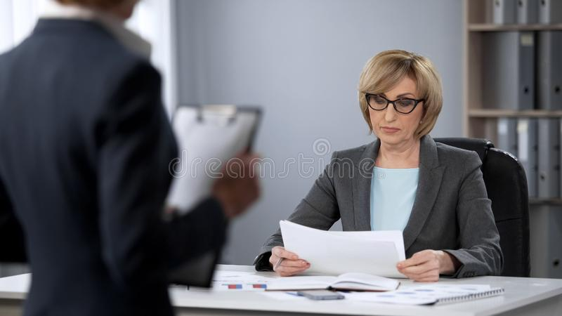 Femme d'affaires sérieuse regardant strictement le secrétaire, dégradation des performances, mauvais travail photographie stock
