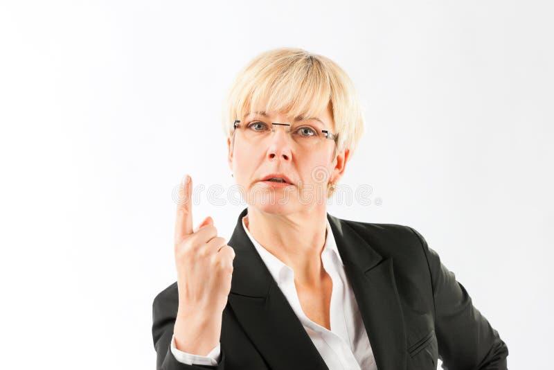 Femme d'affaires sûre dirigeant son doigt vers le haut images stock