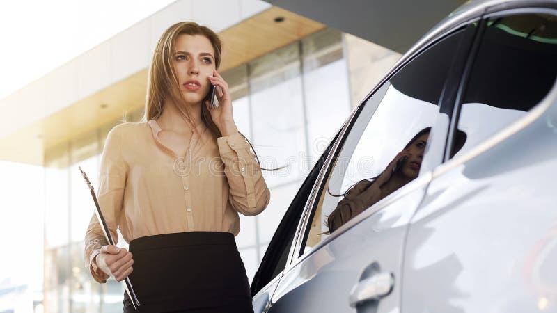 Femme d'affaires sûre parlant sur le smartphone avec la voiture garée proche de client photos stock
