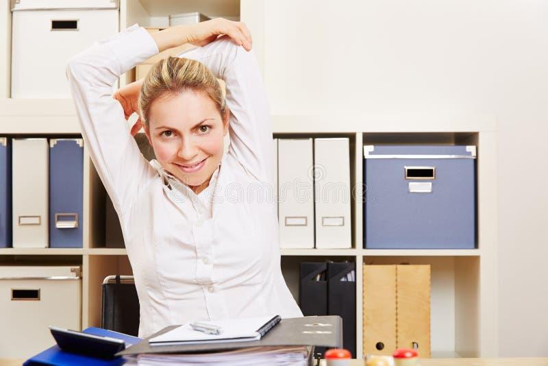 Femme d'affaires s'étirant dans le bureau images libres de droits