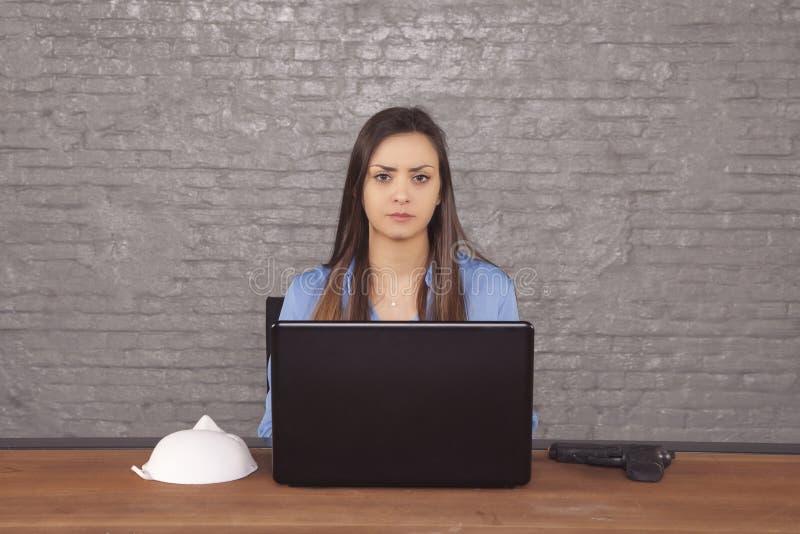 Femme d'affaires s'asseyant à un bureau derrière son ordinateur images stock