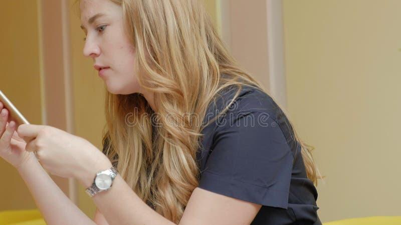 Femme d'affaires s'asseyant à une table dans un café potable de café et aux utilisations sur un smartphone photographie stock