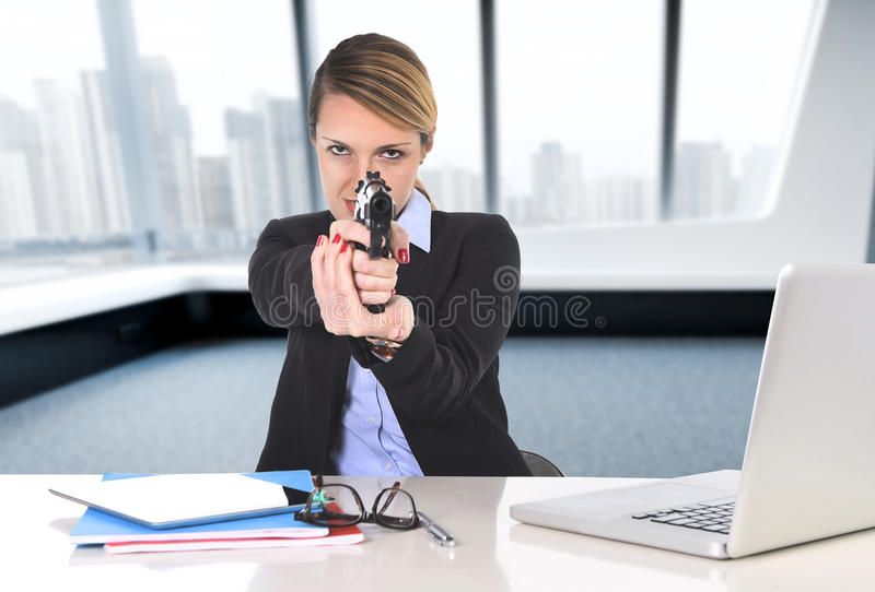 Femme d'affaires s'asseyant au bureau dirigeant l'arme à feu à b puissant images stock
