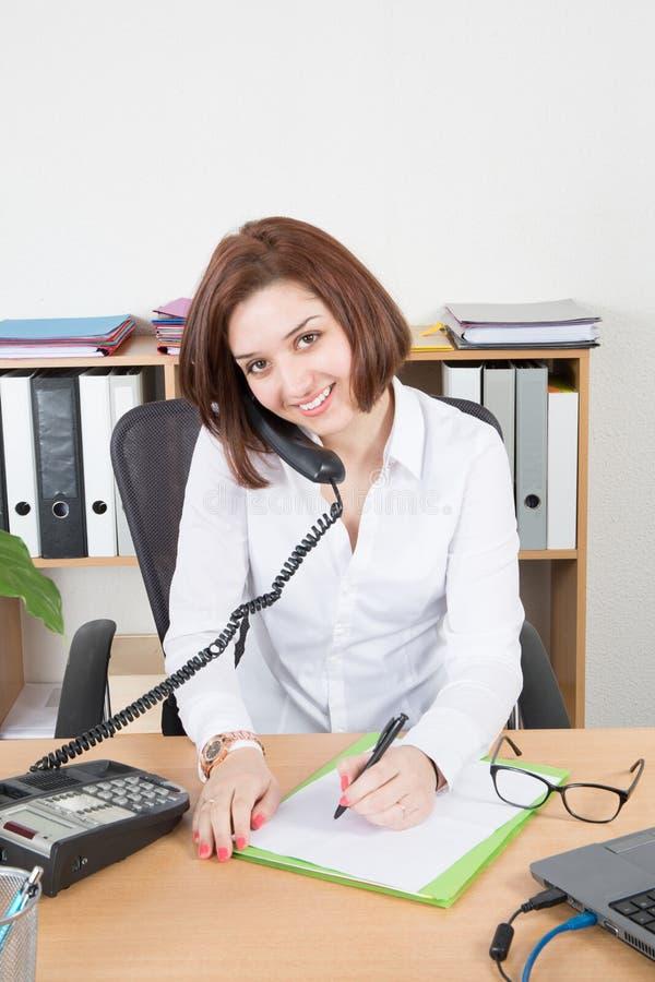 femme d'affaires s'asseyant au bureau et travaillant au téléphone image libre de droits