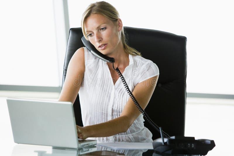 Femme d'affaires s'asseyant dans le bureau avec l'ordinateur portatif images stock