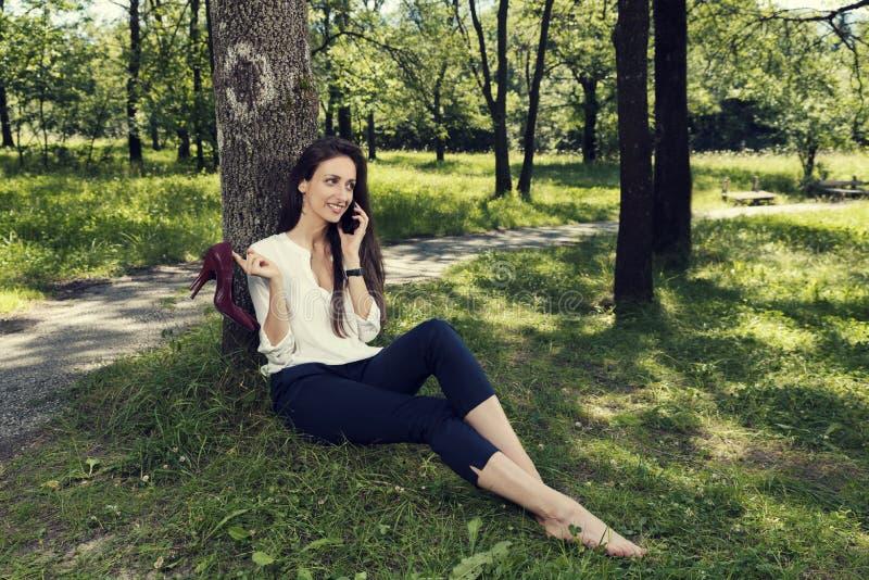 Femme d'affaires s'asseyant sous l'arbre souriant tenant ses chaussures dans sa main et parlant au téléphone en parc public photographie stock