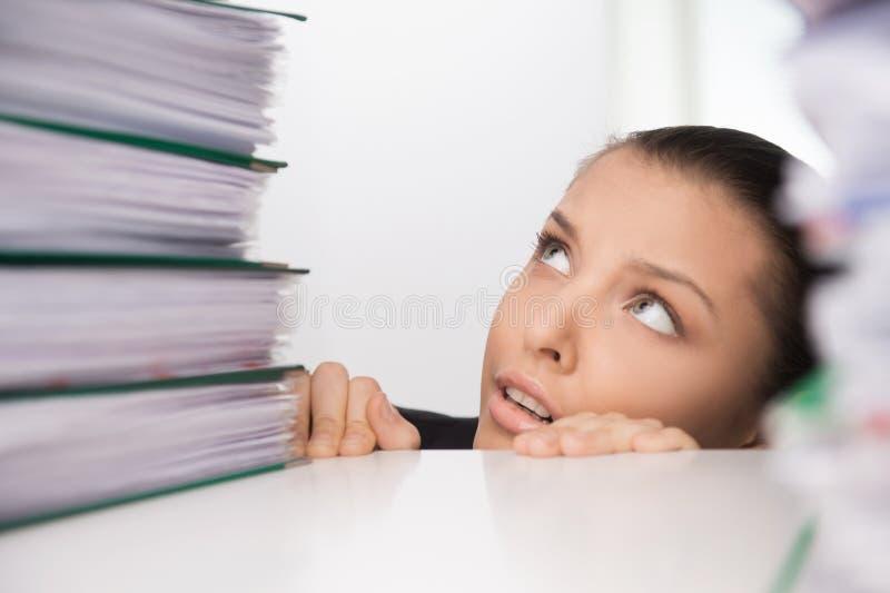 Femme d'affaires s'asseyant sous la table et regardant sur des dossiers photographie stock