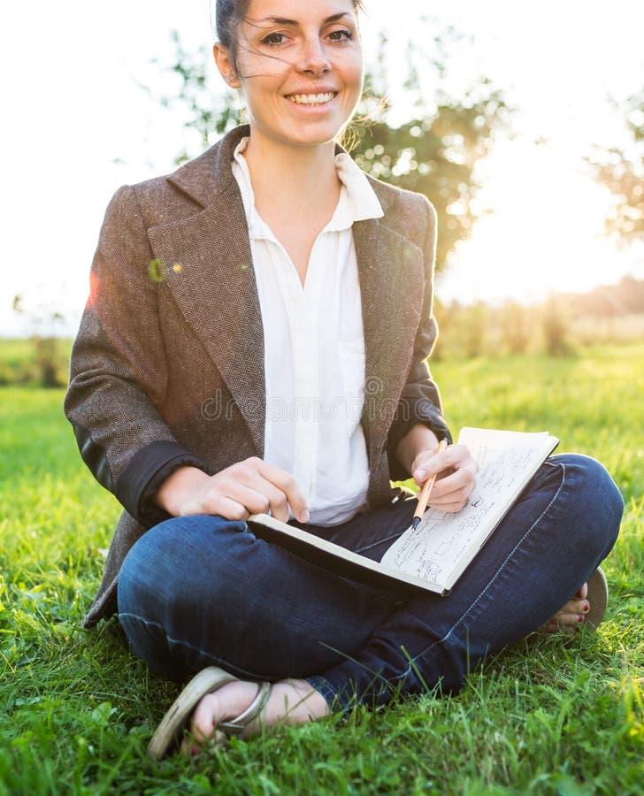 Femme d'affaires s'asseyant sur l'herbe images libres de droits