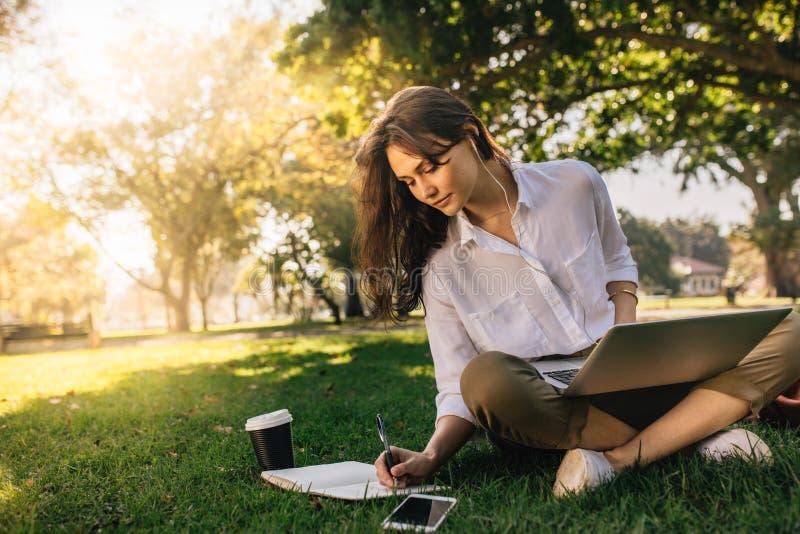 Femme d'affaires s'asseyant sur l'herbe au parc avec l'ordinateur portable et faisant des notes en son journal intime Fonctionnem photos stock