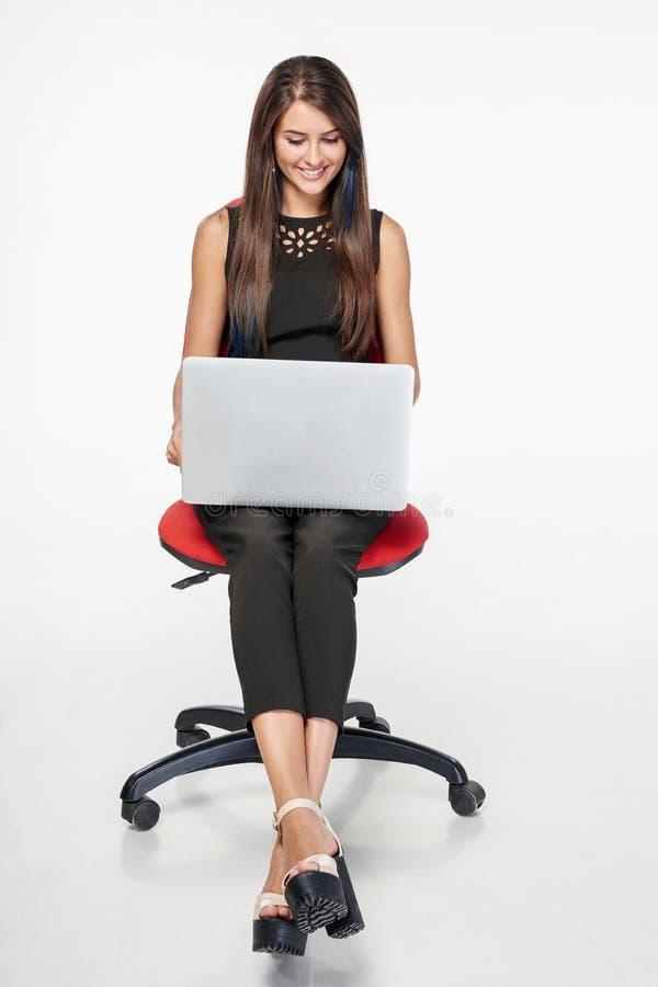 Femme d'affaires s'asseyant sur la chaise de bureau fonctionnant avec l'ordinateur portable image stock