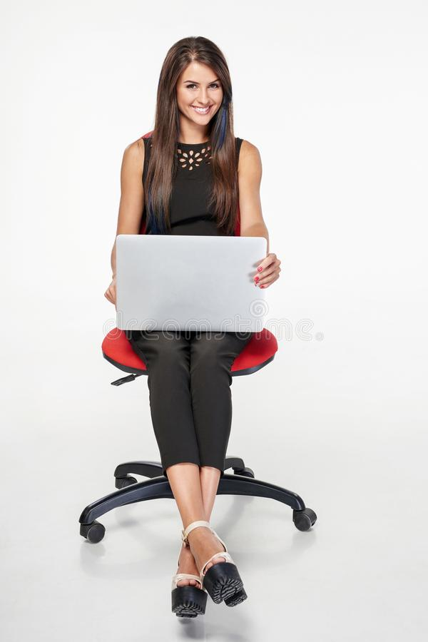 Femme d'affaires s'asseyant sur la chaise de bureau fonctionnant avec l'ordinateur portable photo stock