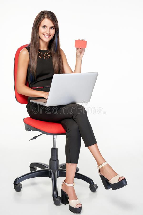 Femme d'affaires s'asseyant sur la chaise de bureau fonctionnant avec l'ordinateur portable photographie stock libre de droits