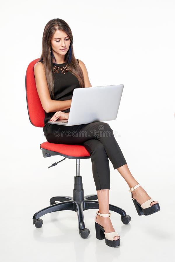 Femme d'affaires s'asseyant sur la chaise de bureau fonctionnant avec l'ordinateur portable photos libres de droits