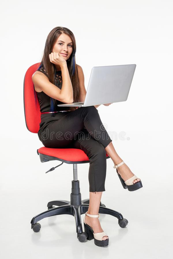 Femme d'affaires s'asseyant sur la chaise de bureau fonctionnant avec l'ordinateur portable photos stock