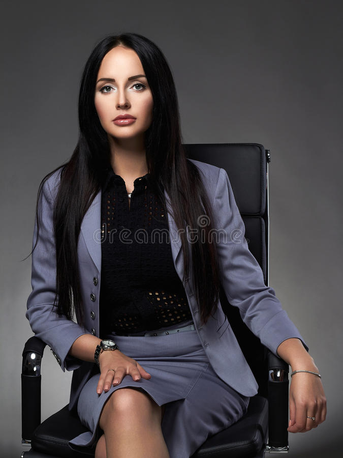 Femme d'affaires s'asseyant sur la présidence photographie stock libre de droits
