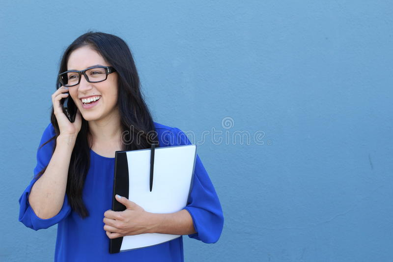 Femme d'affaires sûre heureuse parlant au téléphone portable mobile d'isolement sur le bleu photographie stock libre de droits