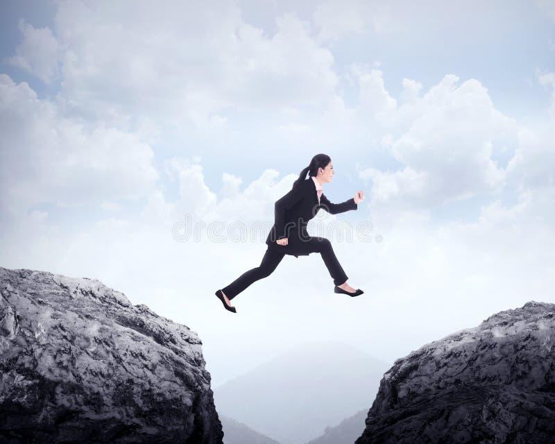 Femme d'affaires sautant à travers la colline photographie stock