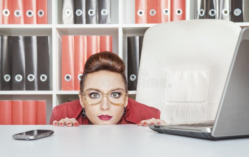 Femme d'affaires se cachant derrière la table et effrayée photographie stock