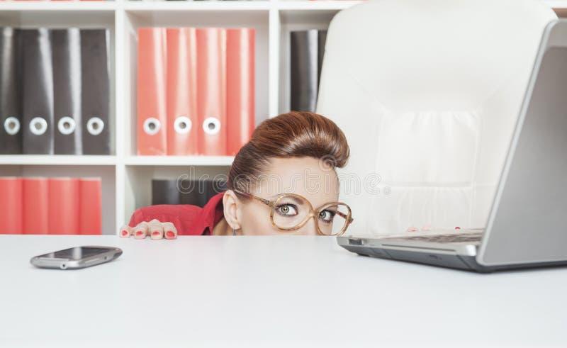 Femme d'affaires se cachant derrière la table et effrayée photo stock