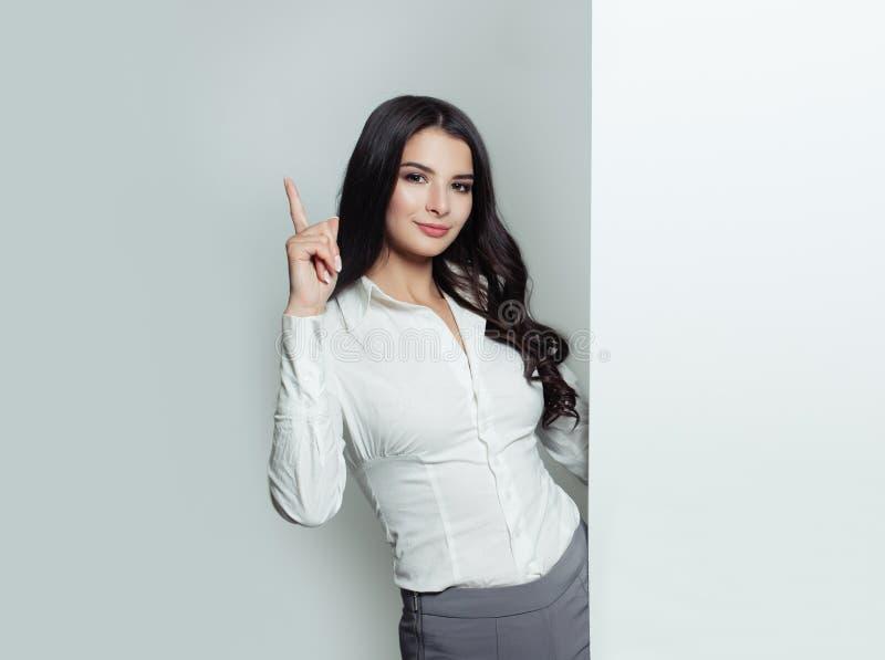 Femme d'affaires se dirigeant et tenant la bannière vide blanche images stock