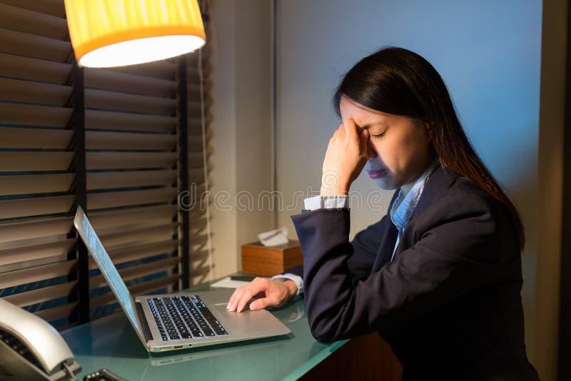 Femme d'affaires se sentant fatiguée en travaillant au-dessus de la nuit image libre de droits