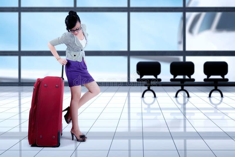 Femme d'affaires se tenant avec des bagages dans l'aéroport images stock