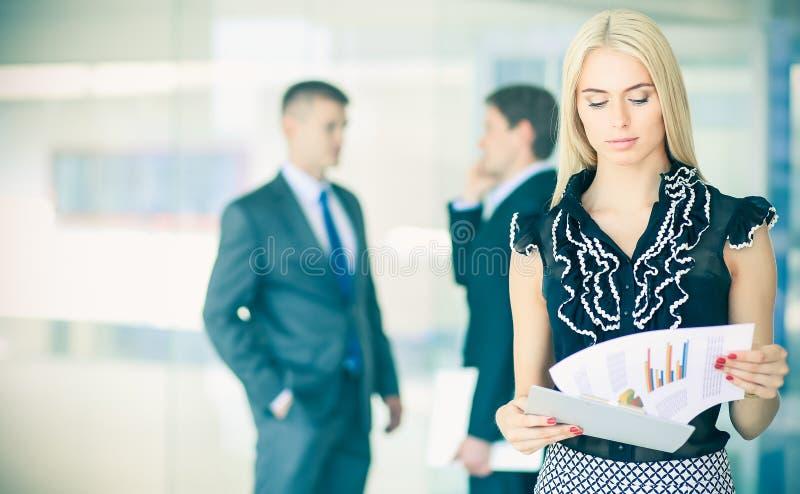 Download Femme D'affaires Se Tenant Dans Le Premier Plan Avec Un Dossier Dans Des Ses Mains Photo stock - Image du mignon, accouplement: 87700996