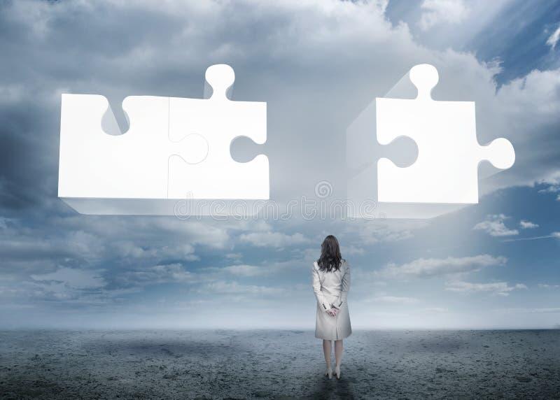 Femme d'affaires se tenant regardante le puzzle denteux photographie stock
