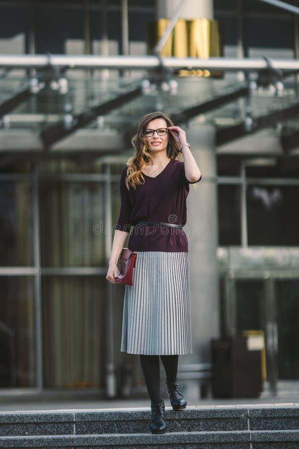Femme d'affaires se tenant sur la rue contre l'immeuble de bureaux Fonctionnement de femme d'affaires de ville Sourire de femme d image libre de droits