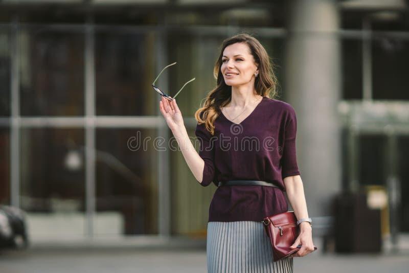 Femme d'affaires se tenant sur la rue contre l'immeuble de bureaux Fonctionnement de femme d'affaires de ville Sourire de femme d image stock