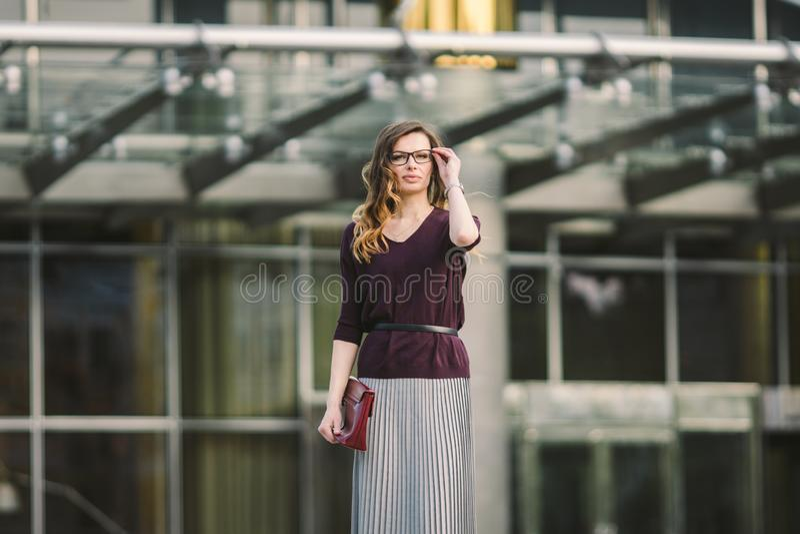Femme d'affaires se tenant sur la rue contre l'immeuble de bureaux Fonctionnement de femme d'affaires de ville Sourire de femme d photo stock
