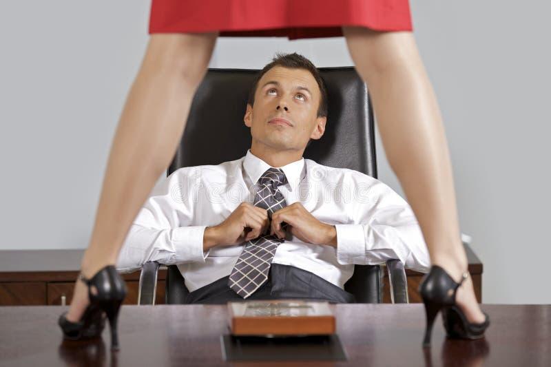 Femme d'affaires se tenant sur la table devant l'homme d'affaires au bureau images stock