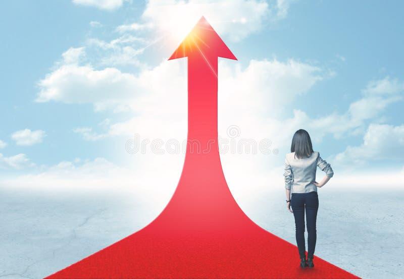 Femme d'affaires se tenant sur une flèche rouge photo stock