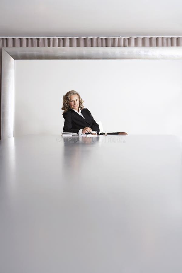 Femme d'affaires Sitting In Boardroom image libre de droits