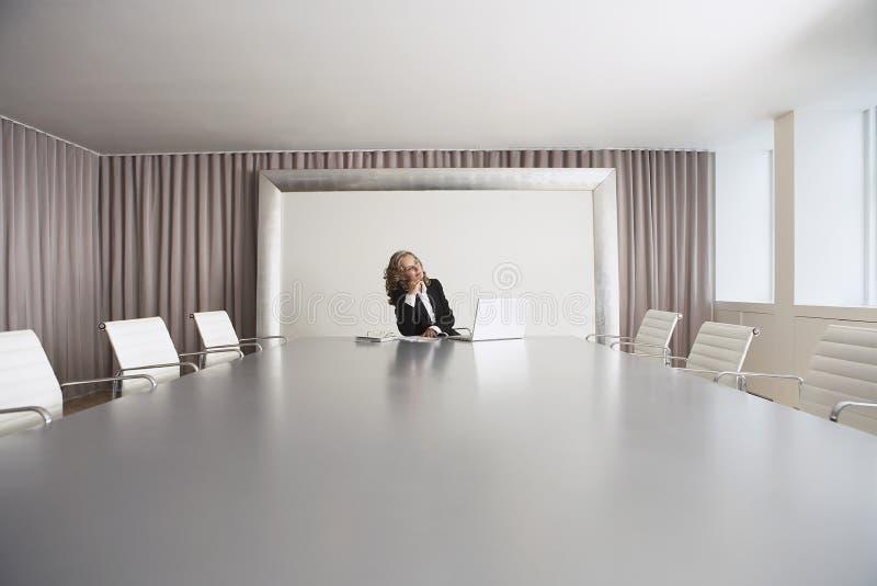 Femme d'affaires Sitting In Boardroom avec l'ordinateur portable image stock