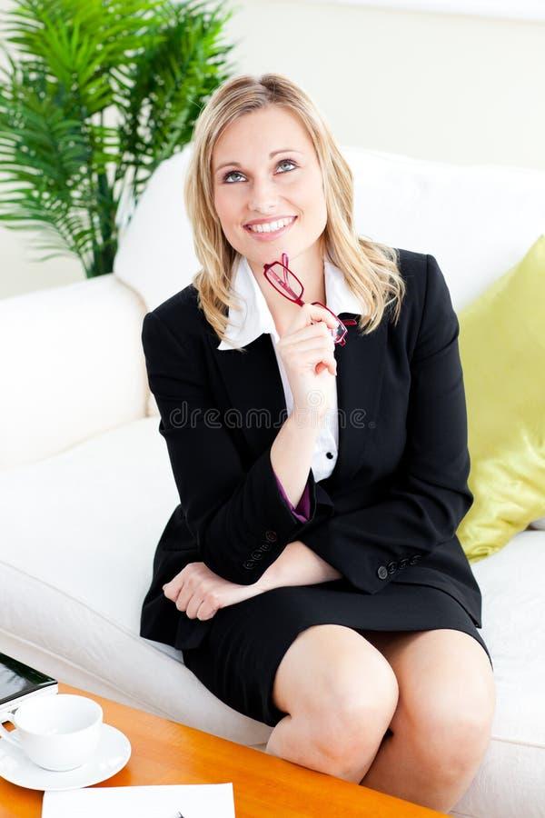 Femme d'affaires songeuse avec des glaces se reposant sur le sofa images stock
